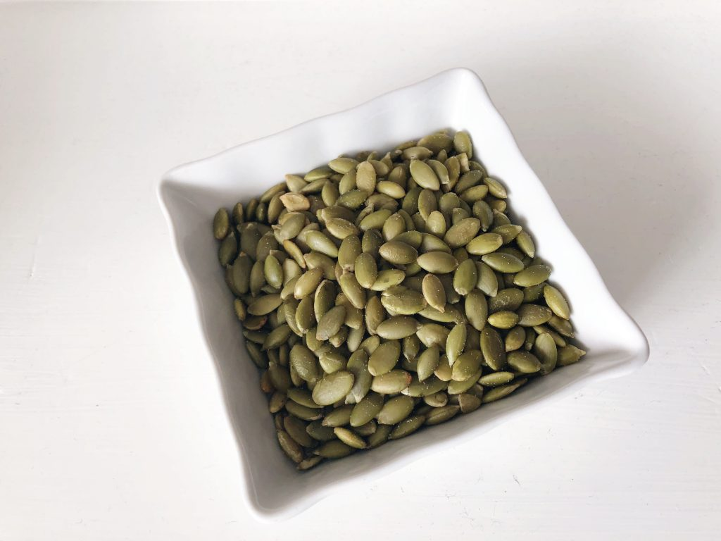 white square dish holding pumpkin seeds