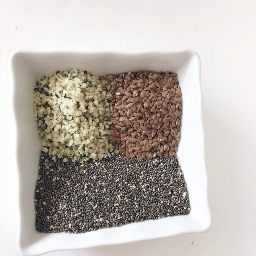white square dish holding hemp seeds, chia seeds and flax seeds