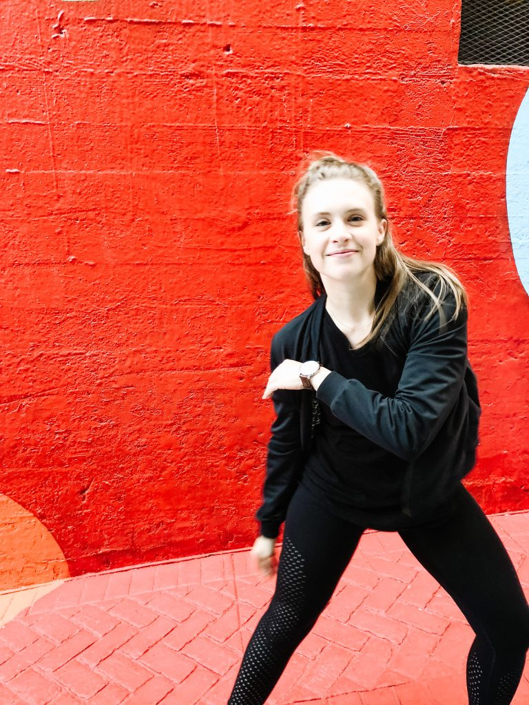 girl dressed in al black in a red alley