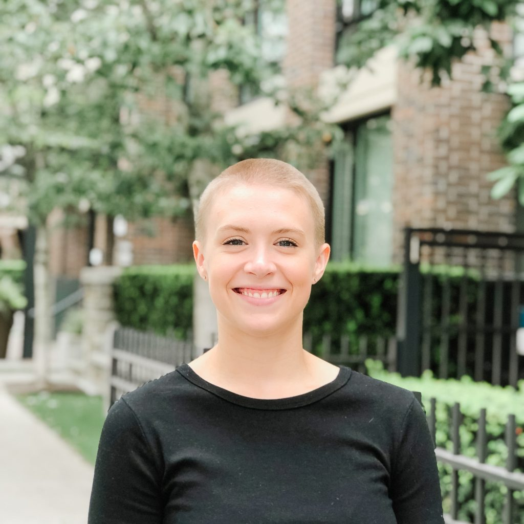 girl smiling with shaved head and black shirt on