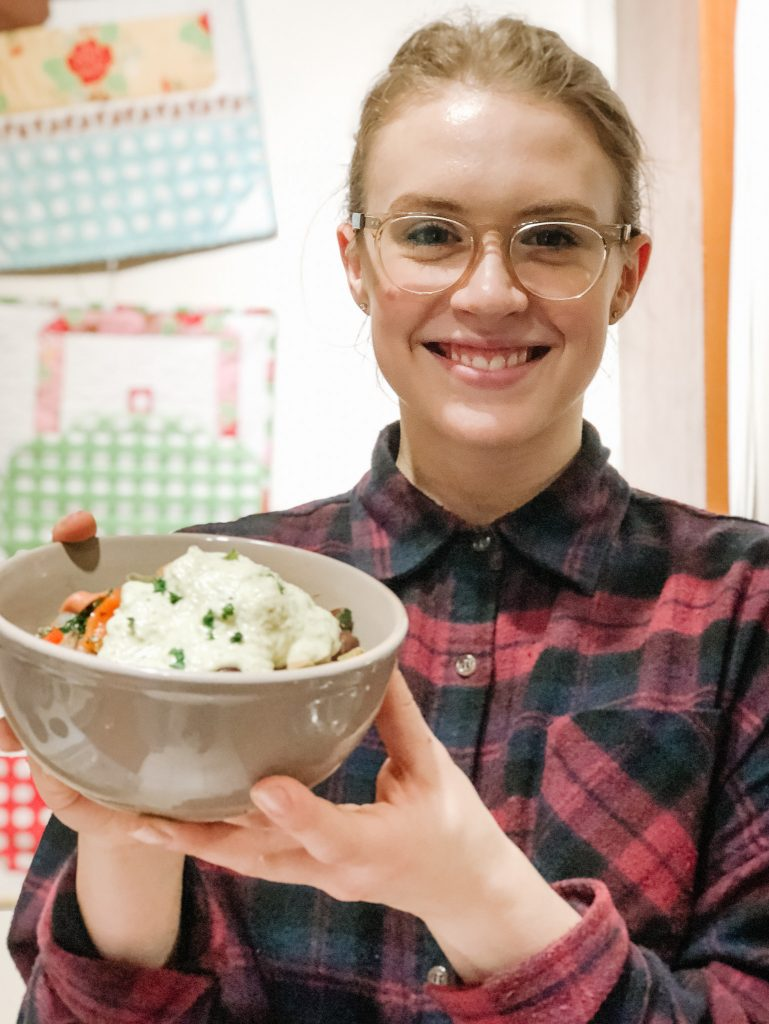 Blonde girl with glasses in plaid shirt holding up bowl of food