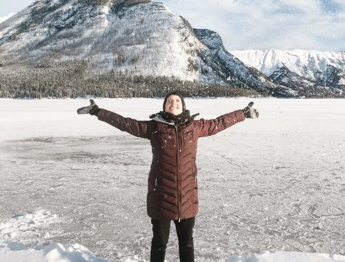 Girl standing on Lake Minnewanka in Alberta, Canada throwing snow